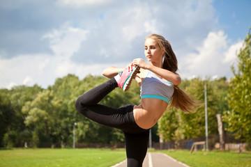 Стройная девушка занимается спортом на природе