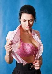 Девушка расстёгивающая блузку