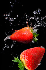 Strawberries falling in water.
