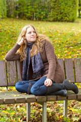 Young woman sitting on a park bench in autum