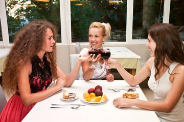 Три красивая девушки пьют вино в кафе, отмечают праздник