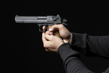 male hands with gun isolated on black background
