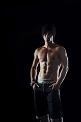 Bodybuilder showing his muscles on a black background