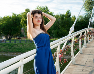 Beautiful young oriental girl on bridge over the river