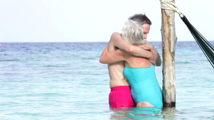 Senior Couple Embracing In The Sea Next To Hammock