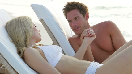 Romantic Couple Relaxing On Loungers At Beach
