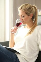 Frau auf Couch mit Weinglas