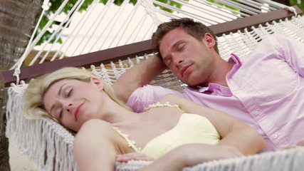 Couple Relaxing In Beach Hammock
