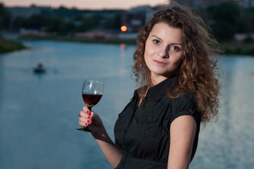Cheerful young girl drinking wine from glass