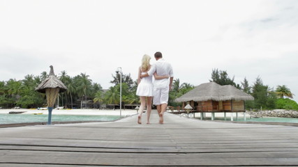 Couple Walking On Wooden Jetty
