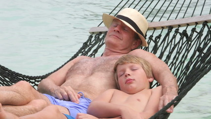 Grandfather And Grandson Relaxing In Beach Hammock