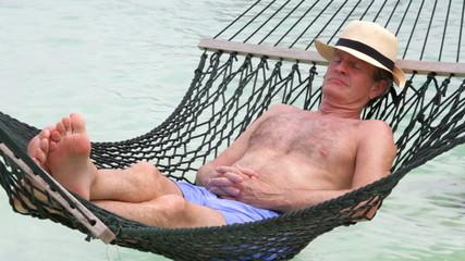 Senior Man Relaxing In Beach Hammock