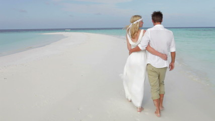 Rear View Of Couple Walking Along Beach At Wedding