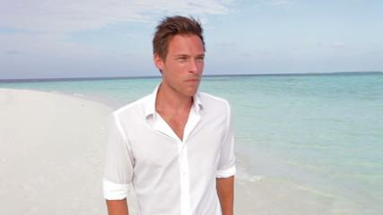 Casually Dressed Man Walking Along Beach