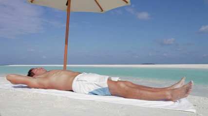 Man Sunbathing On Beach Holiday