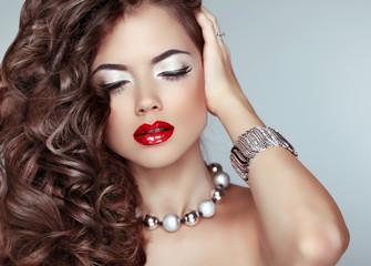 Beauty fashion girl. Long wavy hair. Red lips. Eye Makeup. Jewel