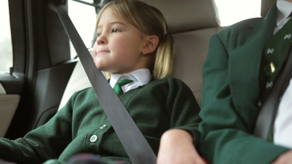 Two Children In Uniform Being Driven To School
