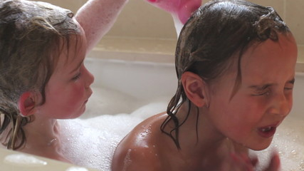 Two Girls Sharing Bubble Bath And Washing Hair