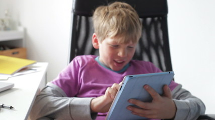Boy Using Digital Tablet In Bedroom