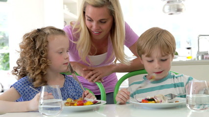 Mother And Children Eating Meal At Home Together