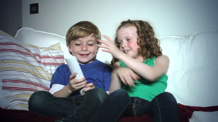 Two Children Sitting On Sofa Arguing Over TV Remote