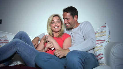 Young Couple On Sofa Watching TV Together
