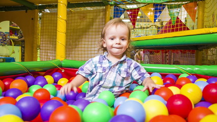 Small  Boy Plays With Multicolored Balls