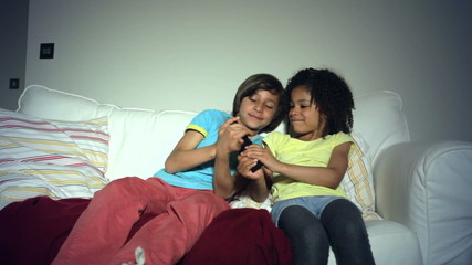 Two African American Children On Sofa Arguing Over TV Remote