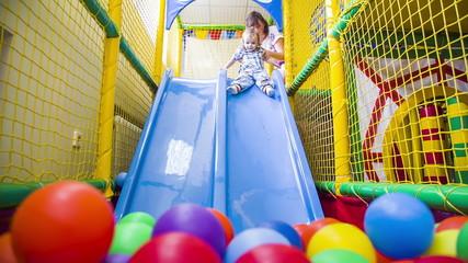Small  boy Sliding Into Multicolored Balls