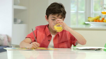 Hispanic Boy Doing Homework On Kitchen Counter