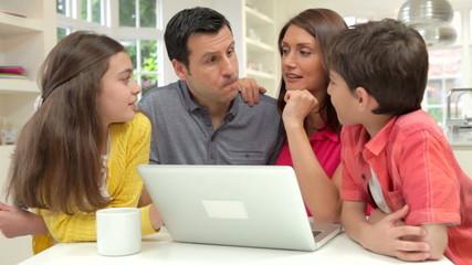 Hispanic Family Using Laptop At Home