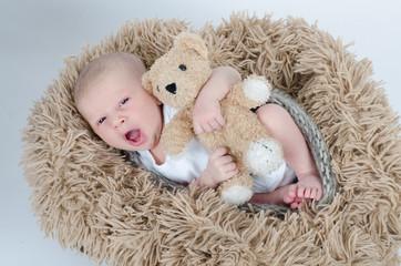 Gähnendes Baby mit Teddy