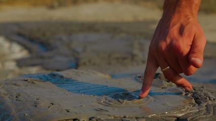 Man Touching Volcano Mud