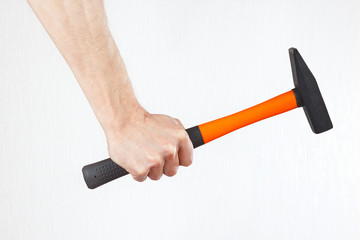 Hand of repairman with a hammer on a white background