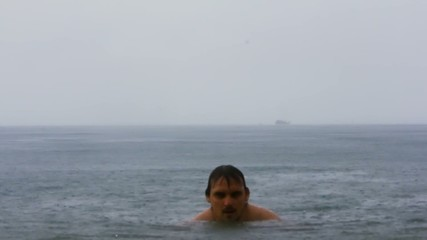 Man dives into the rainy sea in Koh Samui