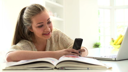 Teenage Girl Sending Text Message Whilst Studying On Laptop