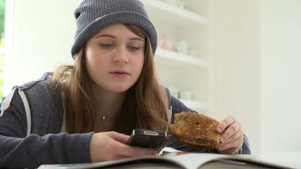 Teenage Girl Having Breakfast Whilst Sending Text Message