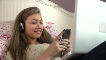 Teenage Girl Lying On Bed Using Laptop Whilst Texting