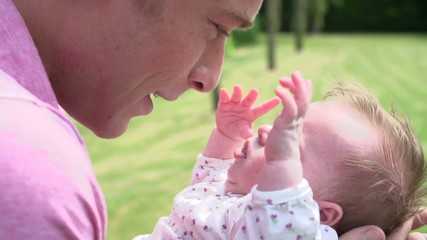 Slow Motion Shot Of Father Holding Baby Daughter In Garden