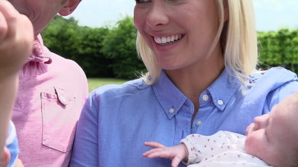 Slow Motion Shot Of Family With Baby Daughter In Garden