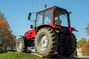 Modern red tractor on a blue sky background. Outdoors.