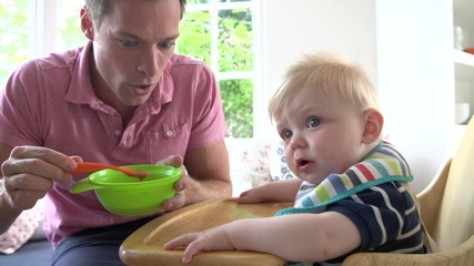 Father Feeding Baby Boy In High Chair
