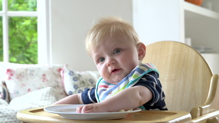 Baby Boy Eating Meal In In High Chair