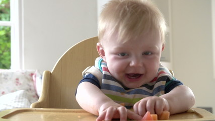 Baby Boy Eating Fruit In In High Chair