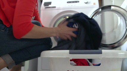 Woman Unloading Clothes From Washing Machine
