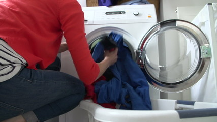 Slow Motion Of Woman Loading Clothes Into Washing Machine