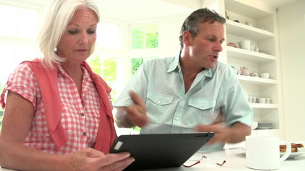 Middle Aged Couple Looking At Digital Tablet Having Argument