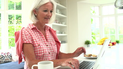 Middle Aged Woman Using Laptop And Eating Breakfast