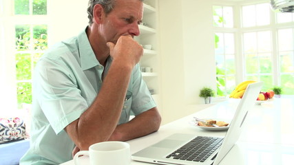 Middle Aged Man Using Laptop And Eating Breakfast