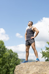 Athletic strong man standing on a rock looking away.